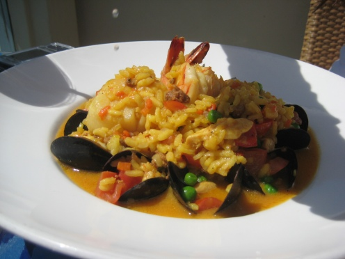 Seafood Paella with prawns, mussels, manila clams, scallops, chorizo, chicken, saffron rice in a seafood broth
